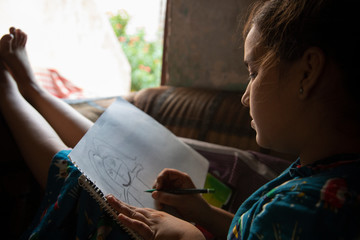 girl sitting on the sofa and drawing on a paper