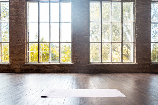 Rolled yoga pilates rubber mat inside gym studio on wooden floor sport workout fitness club class training exercise equipment in clean room interior space bid windows nobody background concept.