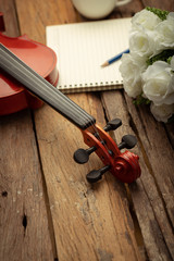 Close-up shot coffee cup and violin orchestra instrumental over wooden background select focus shallow depth of field