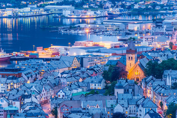 View from Aksla mountain towards Alesund old town and harbour illuminated at dusk, Norway