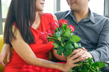 Man giving flowers to his lover on Valentine Day at home.