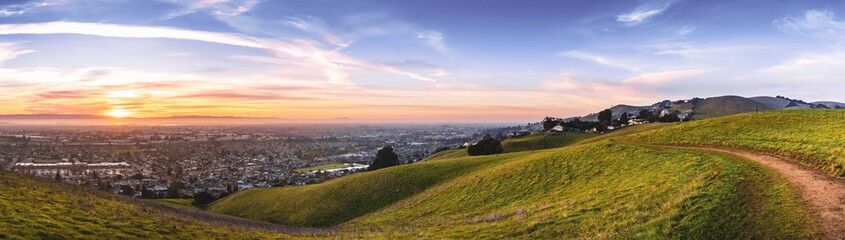 Sunset view of hiking trail on the verdant hills of East San Francisco Bay Area; the city of Hayward and the bay visible in the valley; California Wall mural