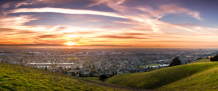 Sunset view of residential and industrial areas in East San Francisco Bay Area; green hills visible in the foreground; Hayward, California
