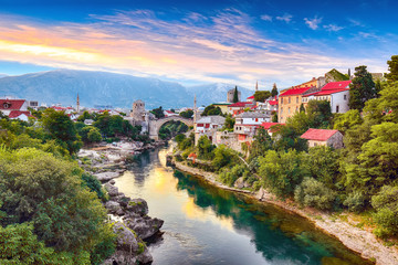 In de dag Oude gebouw Fantastic Skyline of Mostar with the Mostar Bridge, houses and minarets, at sunset