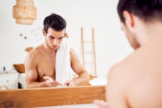 Young sports man with lotion in hands and towel on shoulders stands in front of bathroom mirror
