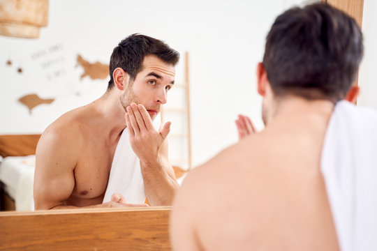 Sportive man lathers face and stands with towel on his shoulders in front of bathroom mirror
