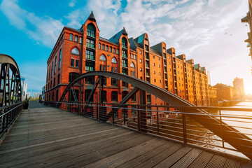 Arch bridge over canals in the Speicherstadt of Hamburg. Warm evening sun light on red brick building