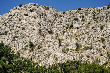 View of the mountains, covered with rare shrubs and grass, surrounding the city of Omis from the northeast side. Croatia