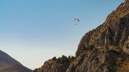 Paraglider flies towards the steep slopes of the mountains against the blue sky, Omis, Croatia