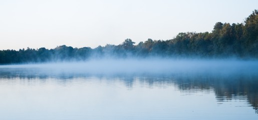 Aluminium Prints Autumn Wide shot of a beautiful lake with a light fog forming above it