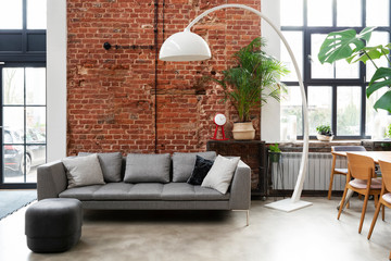 Living room interior in loft apartment in industrial style with brick wall, grey stylish sofa and big window. Modern lamp and design furniture in minimal indoors.