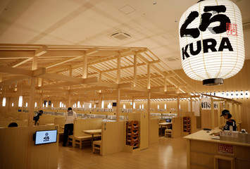Employees work at Kura Sushi's new branch during a media event a day before the official opening in Tokyo