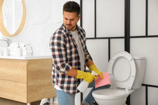 Young man feeling disgust while cleaning toilet bowl in bathroom