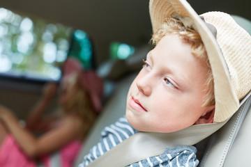 Junge sitzt müde auf der Rückbank im Auto