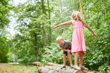 Kinder spielen auf Baumstämmen im Wald