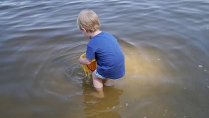 Dziecko bawi się w wodzie. Chłopiec bawi się wiaderkiem i stoi w wodzie.