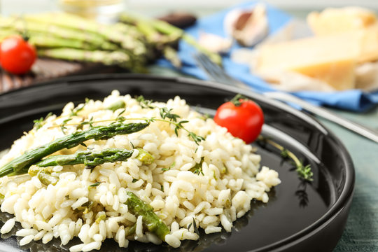 Delicious risotto with asparagus on table, closeup