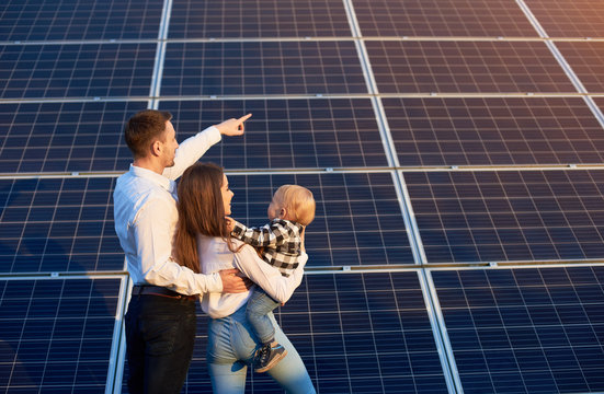 Husband shows his family the solar panels on the background. Blond child in arms of wife. Young family keeps up with the times choosing solar heating