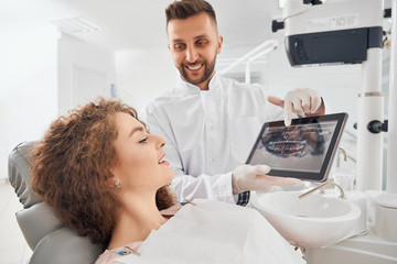 Male doctor showing x-ray pictures of teeth on tablet