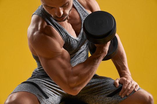 Muscular young gentleman pumping up biceps