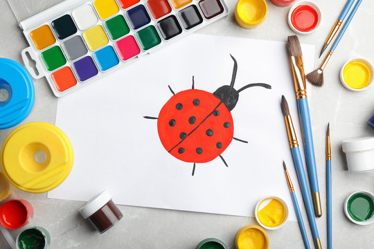 Flat lay composition with child's painting of ladybug on marble table