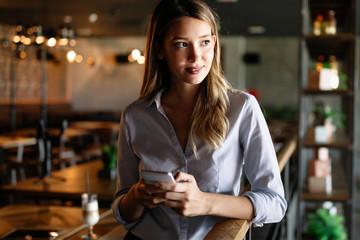 Wall Mural - Beautiful brunette coworker businesswoman talking on mobile phone