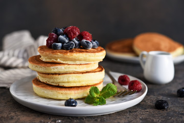 Beautiful pancakes with berries and sauce on a dark concrete background.