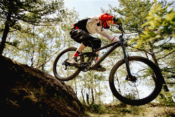 athlete rider riding forest trail in competition downhill