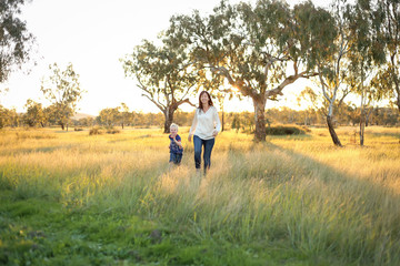 Mother and son playing together in a picturesque field with long grass at sunset. Family time. Mother-son bond. Beautiful image for mother's day with copy space.