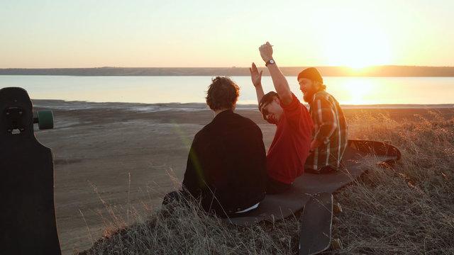 Friends have fun sitting at sea coast sunset