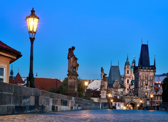 Fotomurales - Charles Bridge at dawn, silhouette of Bridge Tower and saint sculptures with lit street light lamp in Prague, Czech Republic