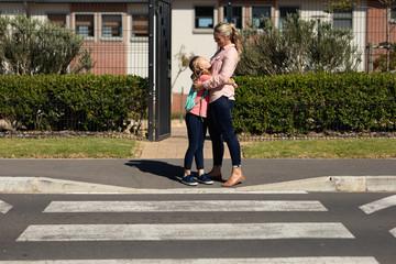 Caucasian schoolgirl and her mother embracing