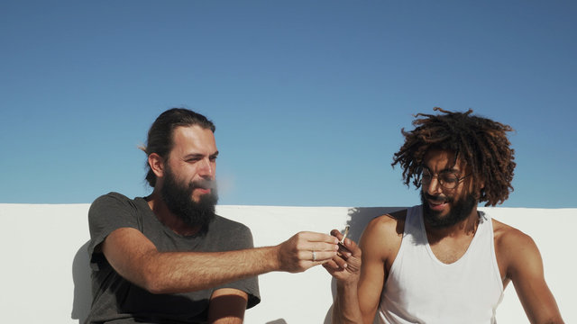 Multi race friends give each other a joint with weed at rooftop blue sky