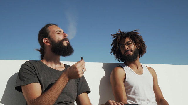 Multicultural friends have fun and smoke weed at rooftop blue sky at backdrop