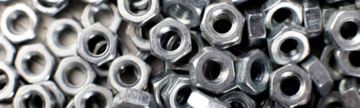 Banner of Metal nuts background. Macro. Working tools. Fixing elements.