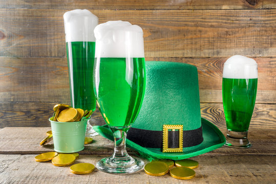 Traditional irish alcohol for St Patrick's day party. Different glasses with green beer, with golden chocolate coins decor and green leprechaun hat. Old rustic wooden background copy space