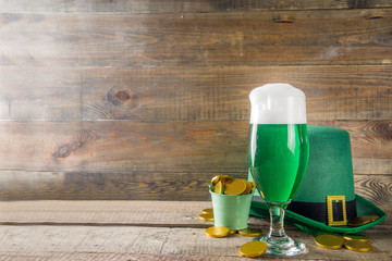Foto op Plexiglas Alcohol Traditional irish alcohol for St Patrick's day party. Different glasses with green beer, with golden chocolate coins decor and green leprechaun hat. Old rustic wooden background copy space