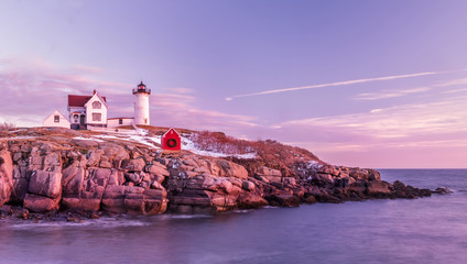 Poster - A tender morning with pink clouds on the coast of the Atlantic Ocean. lighthouse located on a rocky rock in the water. Long exposure.  Atlantic Ocean. USA. Maine.  Nubble york