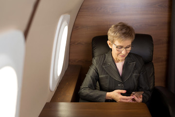 beautiful stylish woman aged, in the cabin of a private plane with a phone in her hand