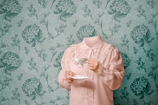 Woman with no head holding tea cup while standing against wall