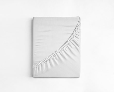 Flat sheet or bed cover folded. White fitted sheet isolated. White sheet with elastic band.
