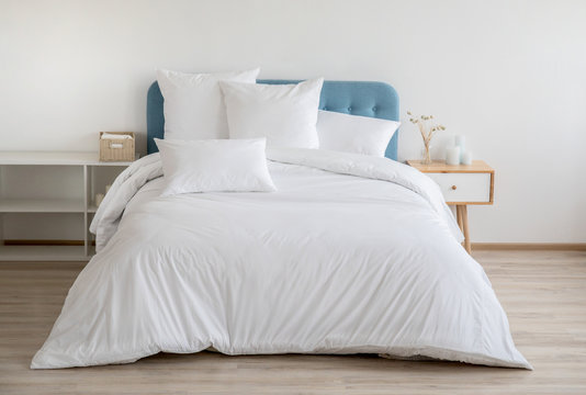 Interior with white bed linen on the sofa. Bedroom with bed, white bedding, and bedside table. White pillows, duvet and duvet case on bed with blue headboard. Front view.