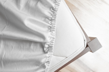 Bed corner with white fitted sheet. White sheet with elastic band. Flat sheet or bed cover.