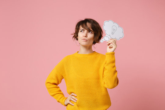 Pensive young brunette woman girl in yellow sweater posing isolated on pastel pink background studio portrait. People lifestyle concept. Mock up copy space. Hold say cloud with lightbulb, looking up.