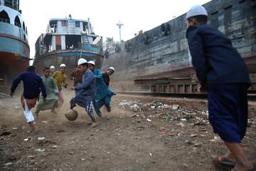 Children play football in a dockyard in Dhaka