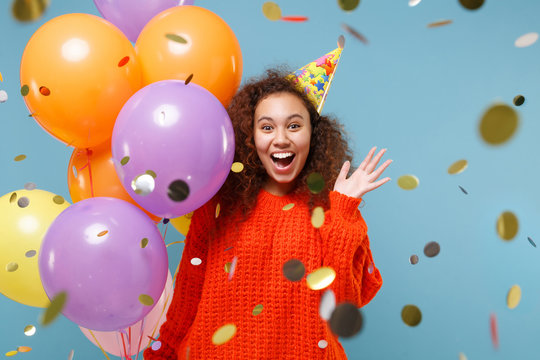 Amazed young african american girl in orange knitted clothes birthday hat isolated on pastel blue background. Holiday party concept. Celebrating with confetti, colorful air balloons spreading hands.