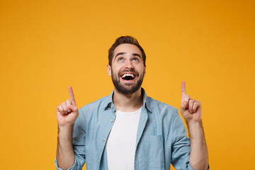 Cheerful young bearded man in casual blue shirt posing isolated on yellow orange background studio portrait. People sincere emotions lifestyle concept. Mock up copy space. Pointing index fingers up.