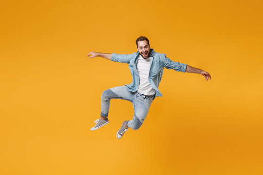 Cheerful young bearded man in casual blue shirt posing isolated on yellow orange background, studio portrait. People sincere emotions lifestyle concept. Mock up copy space. Jumping spreading hands.