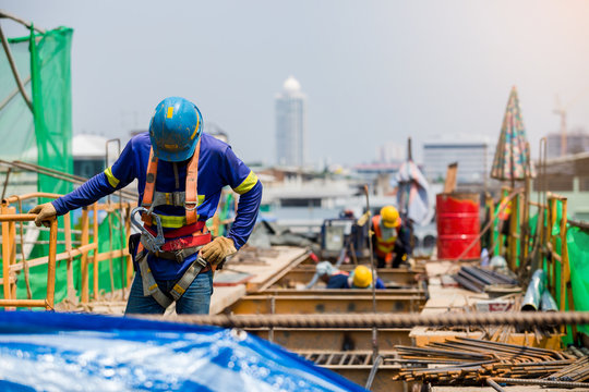 Builder worker in safety protective equipment. Professional industrial climber in helmet and uniform works at height. Risky extreme job. Industrial climbing at construction site.