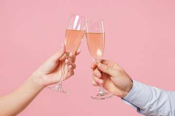 Close up cropped photo of female, male hold in hands glass of champagne isolated on pastel pink background. Copy space advertising mock up. Valentine's Day Women's Day birthday holiday party concept.